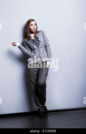 Le modèle de mode. Jeunes et belles dans womqn posant en costume gris studio Banque D'Images