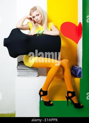Femme élégante cheveux blonde posing in studio avec mannequin noir Banque D'Images