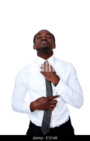 Homme africain ajustant sa cravate sur fond blanc Banque D'Images