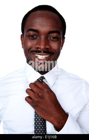Heureux homme africain ajustant sa cravate sur fond blanc Banque D'Images