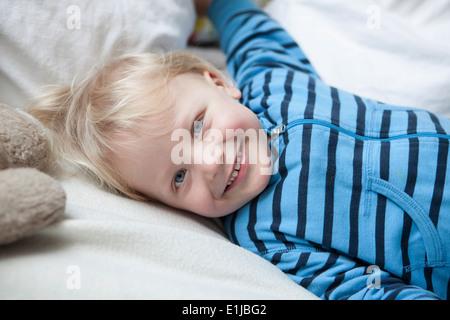 Portrait of smiling little boy lying on blanket Banque D'Images