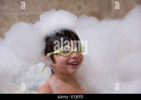 Portrait de jeune garçon portant ces lunettes in bubble bath