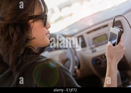 Jeune femme de la lecture de texte sur son portable dans... Banque D'Images