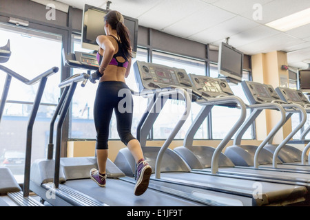 Mid adult woman running on treadmill in gym Banque D'Images