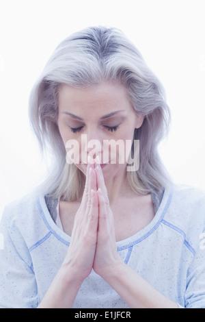 Femme mature pose dans la prière Banque D'Images