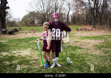 Brother and sister wearing lacrosse uniforms Banque D'Images