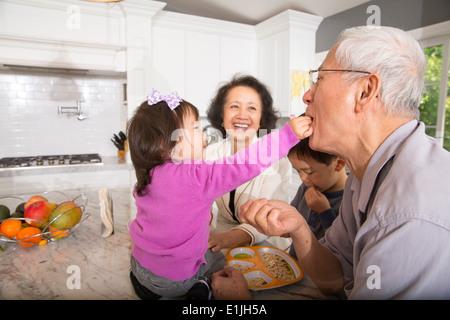 Les repas des tout-petits de sexe féminin à grand-père en cuisine snack Banque D'Images