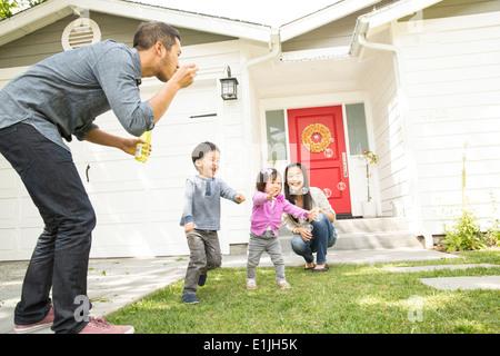 Couple avec deux enfants blowing bubbles Banque D'Images