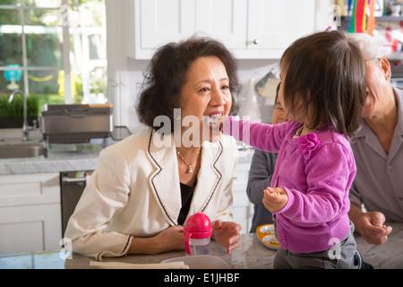 Les repas des tout-petits de sexe féminin à grand-mère en cuisine snack Banque D'Images