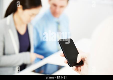 Personne à l'aide de collègues, smartphone en arrière-plan Banque D'Images