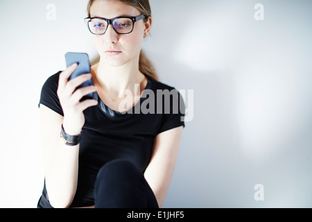 Young woman wearing glasses using smartphone Banque D'Images