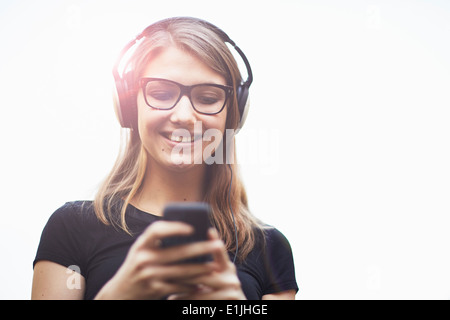 Young woman wearing headphones using smartphone Banque D'Images