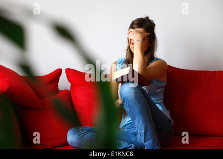 Jeune femme lisant la Bible à la maison. Banque D'Images