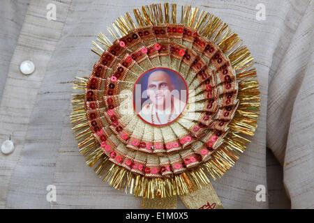 Dévot portant un bouton avec un portrait du leader spirituel Swami Giri Avdeshanand Banque D'Images