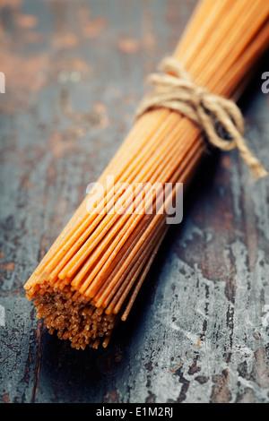 Spaghetti de blé entier sur fond de bois Banque D'Images