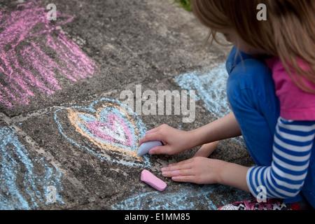 Un dessin de fille coeur de craie sur un trottoir en béton. Banque D'Images