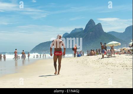 RIO DE JANEIRO, Brésil - Mars, 2013: Jeune homme musclé brésilien promenades le long de la plage d'Ipanema en rouge Banque D'Images