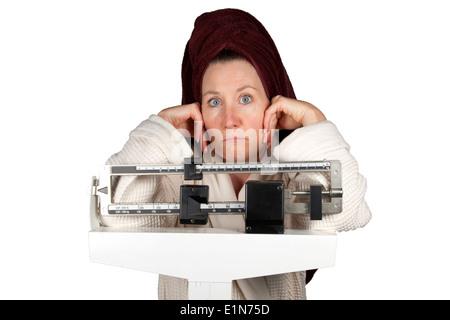 Young woman in bathrobe debout sur une balance de salle à perplexe Banque D'Images
