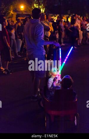 Garden City, New York, USA. 6 juin, 2014. Le soir, une jeune fille et garçon tenir des bâtons lumineux colorés comme Banque D'Images