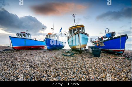 Bateaux de pêche sur une plage de galets à la bière dans le Devon Banque D'Images