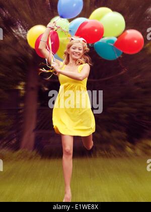 Happy young woman in robe d'exécution avec des ballons colorés Banque D'Images