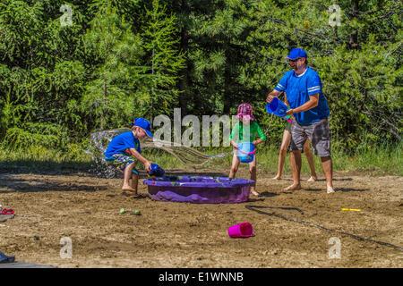 Les enfants et adultes dans une lutte , l'eau playfull sur un jour d'été chaud et ensoleillé. Cranbrook, Colombie Banque D'Images