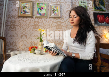 Beautiful young woman reading book in cafe Banque D'Images