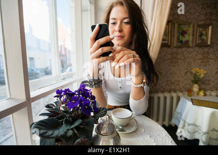 Young woman using smart phone at cafe table Banque D'Images