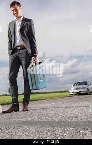 Toute la longueur du jeune homme transportant du gaz peut avec voiture décomposée en tâches de fond à campagne