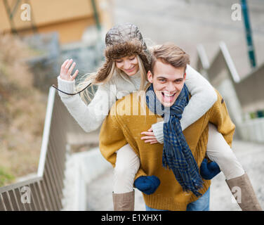 Portrait of cheerful man piggybacking woman on stairway Banque D'Images