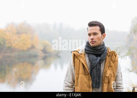 Young man in vêtements chauds debout contre lake Banque D'Images