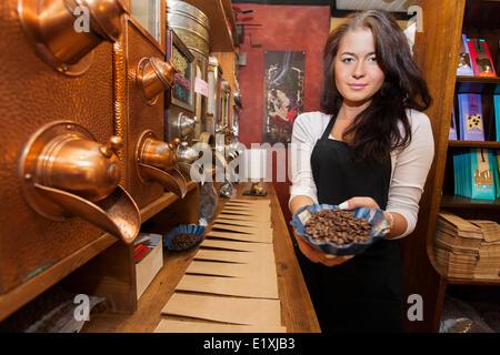 Portrait de femme vendeur montrant des grains de café frais dans le magasin Banque D'Images
