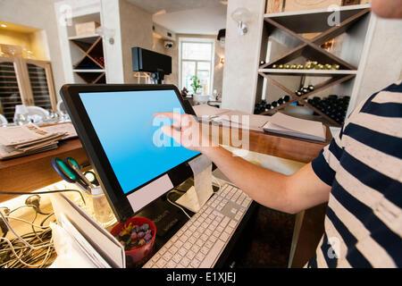 Image recadrée de caissier de toucher l'écran d'ordinateur au restaurant counter Banque D'Images