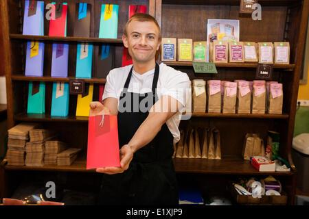 Portrait d'homme vendeur montrant produit en magasin café Banque D'Images
