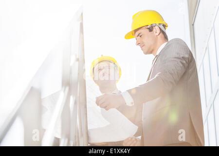 Low angle view of young businessman dans le casque de l'examen de plan directeur pour escalier