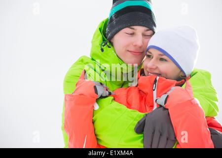 Jeune couple d'amour dans des vêtements chauds embracing outdoors Banque D'Images