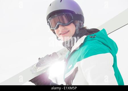 Portrait of smiling young man carrying skis contre ciel clair Banque D'Images