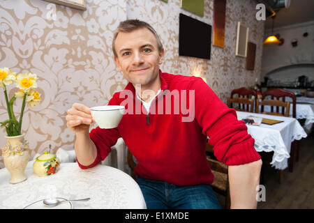 Portrait of happy young man holding Coffee cup at cafe Banque D'Images