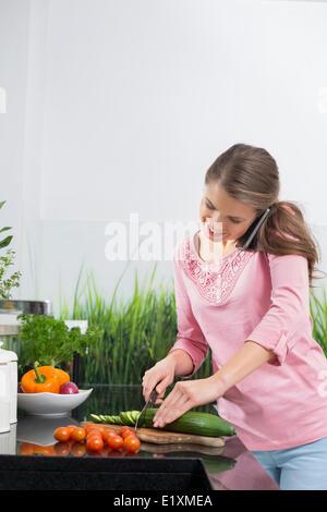 Smiling woman using cell phone tout en réduisant le concombre au comptoir de la cuisine Banque D'Images