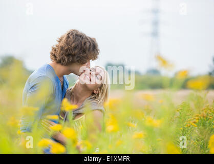 Homme romantique kissing woman in field Banque D'Images