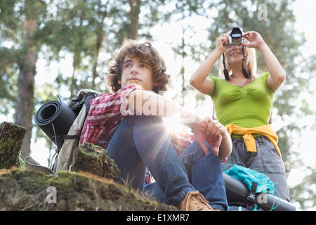 Young female hiker photographing par appareil photo numérique tandis que l'homme à l'écart dans la forêt Banque D'Images