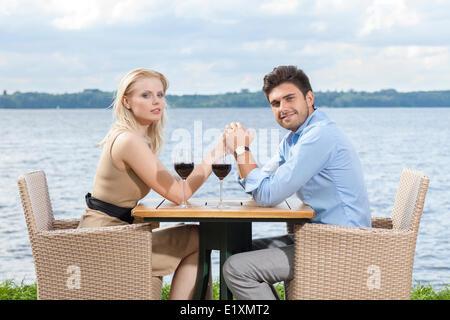 Vue de côté portrait of young couple holding hands at outdoor restaurant by lake Banque D'Images