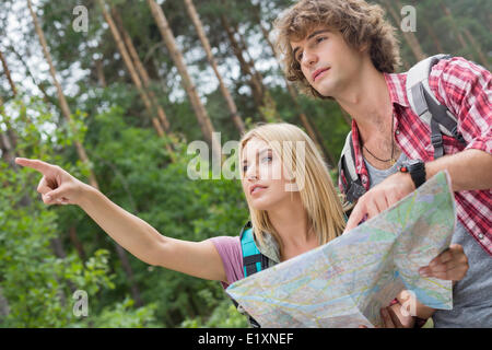 Randonnées couple with map discussing over direction in forest Banque D'Images