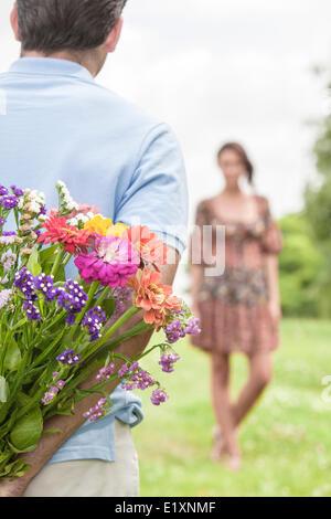 Portrait of female friends with bouquet in park Banque D'Images