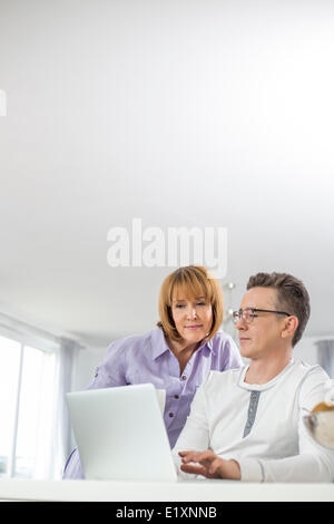 Mature couple using laptop together at home Banque D'Images
