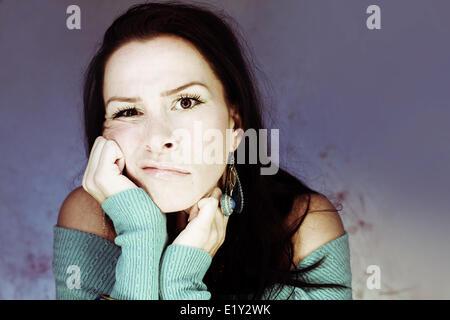 Jolie jeune femme la tête dans les mains s'ennuyer Banque D'Images