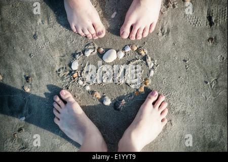 Pieds de couple aimant et un cœur fait Of les coquillages sur le sable sur la plage Banque D'Images
