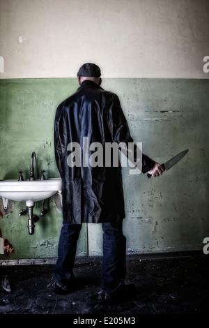 Un homme en vêtements sombres avec un couteau dans une maison abandonnée Banque D'Images