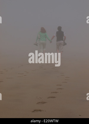 Couple d'âge moyen marche main dans la main dans la mer d'épaisseur de la brume, Padstow, Cornwall, UK Banque D'Images
