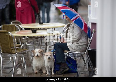 Une femme avec un parapluie Union Jack se trouve à l'extérieur d'un café sous la pluie, avec une tasse de thé. Banque D'Images